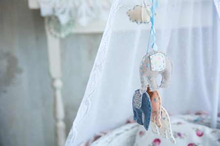 Closeup of soft toys hanging on a cot.