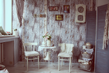 Retro interior with chairs and cups of tea. Background with antique wooden walls for a quiet party together. A room in a reddish tint