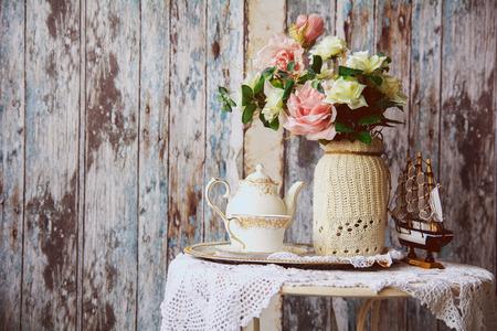 磁器ティーポットと古い木の壁の背景に人工の花と花瓶とテーブルの上のカップ。テーブルの上の小さなボート 写真素材