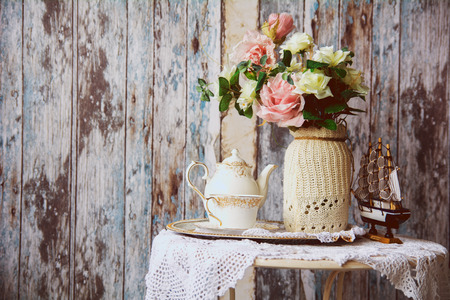 boat party: Porcelain teapot and cup on a table with a vase with artificial flowers on a background of the old wooden walls. Small boat on the table