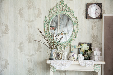 Vintage interior with mirror and a table with a vase and willows. Designer wall clock. Angels on the table photo