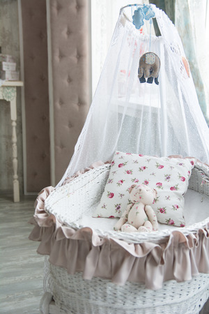 teddy bear baby: Retro interior childrens bedroom with a wicker crib and teddy bear. Stock Photo