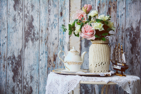 house party: Porcelain teapot and cup on a table with a vase with artificial flowers on a background of the old wooden walls. Small boat on the table