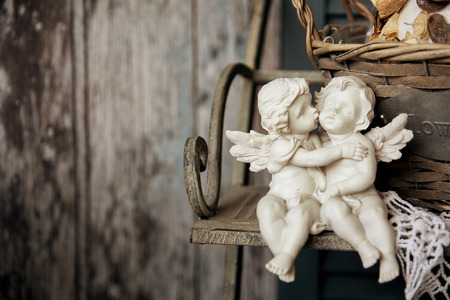 angel girl: Figurines angels sitting on a bench. Romance on the background of old boards Stock Photo