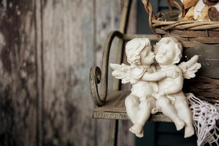 angeles bebe: Figurines ángeles sentados en un banco. Romance en el fondo de tablas viejas Foto de archivo