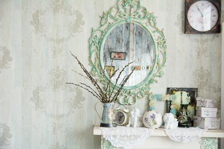 빈티지 거울 인테리어와 꽃병과 버드 나무가있는 테이블. 디자이너 벽 시계. 테이블에 천사