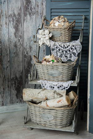 romantic background: Background rustic veranda with a shelf with baskets and angels. Old decorations and wooden walls