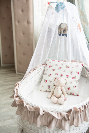 bassinet: Retro interior childrens bedroom with a wicker crib and teddy bear. Stock Photo