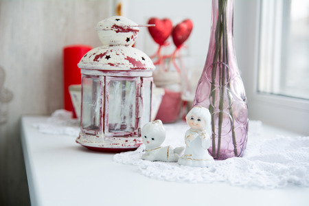 windowsill: Close-up of porcelain figurines with flowers on the windowsill and old lantern for candles. Stock Photo