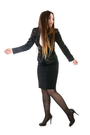 Business woman in full growth is looking back. Asian model in a black suit and pantyhose. Isolated on a white background