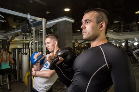 abdominal wall: Kettlebell swing training of two young men in the gym. Stock Photo