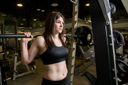 Young girl in the gym with a barbell. Woman trains his muscles on the simulator. Fitness, CrossFit