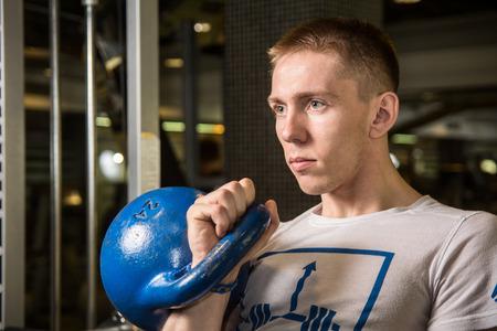 boy gymnast: Kettlebell swing workout training man at gym. Man preparing to CrossFit