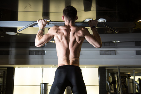 lats: Fitness man doing pull-ups in a gym for a back workout.