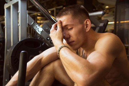 Young athlete sitting on gym equipment with hands on the forehead and resting after fitness training, sad athlete tired to act pensively sitting at gym Stock Photo