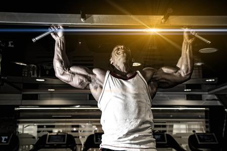 Handsome muscular man in gym making elevations. Bodybuilder training in gym