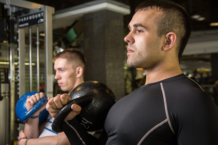 abdominal wall: Kettlebell swing training of two young men in the gym. Young men trained muscles