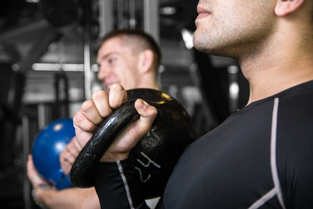 abdominal wall: Close-up kettlebell swing training of two young men in the gym. Young men trained muscles. Preparing for competition