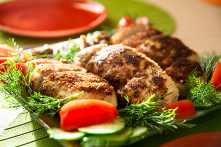 breading: Breading chicken cutlets on a plate with dill tomatoes and cucumbers.