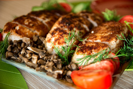 breading: Breading chicken cutlets on a plate with dill cucumbers, tomatoes and mushrooms.