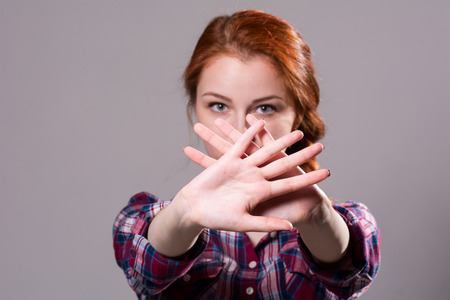 Out of focus woman with her hands signaling to stop isolated on a grey background.