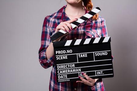 camara de cine: Primer plano de una niña con un azote de la película. Muchacha con camisa a cuadros ayuda en el rodaje de una película