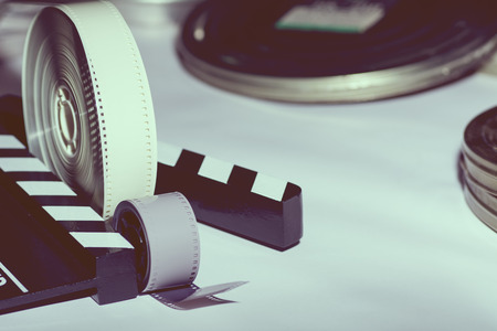 reel: Two rolls of film, boxes of film and cinema slapstick. toned image