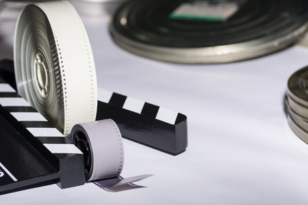 cine: Two rolls of film, boxes of film and movie clapper. Stock Photo