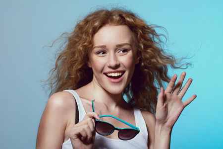 sexual position: Young beautiful fashion girl smiling with his hand raised and sunglasses in hand. Emotional females with curly hair looking away