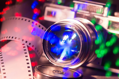 telephoto: Close-up of old photo camera with metallic color. Tape 35 mm movie film. Bright multi-colored reflections Stock Photo