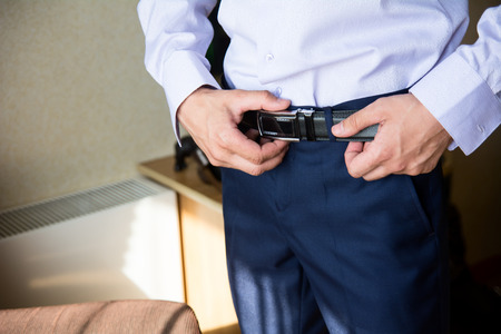 waistband: Close-up of a man adjusts his belt on his trousers. Preparations for celebrations, meetings, weddings Stock Photo