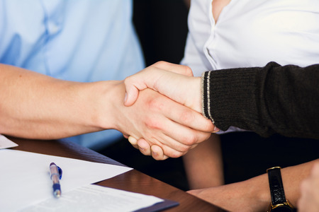 apreton de manos: Apretón de manos de dos hombres de negocios en el fondo de la Secretaria de la mujer después de la firma del contrato. Foto de archivo