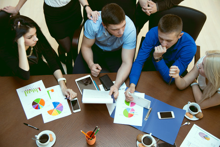 pcs: Top view of a group of young people at a business meeting schedules with phones and tablet PCs. Stock Photo