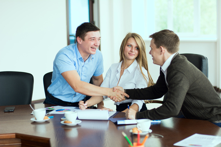 Smiling man at a business meeting shaking hands with each other in the office in the presence of a business woman. Standard-Bild