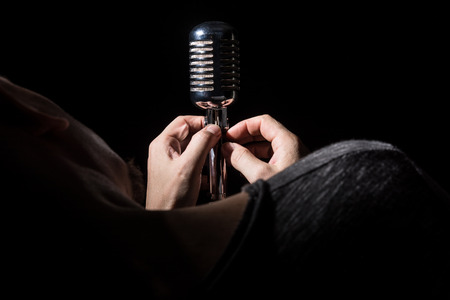 sings: Close-up singer song prepares microphone sings a song. Stock Photo