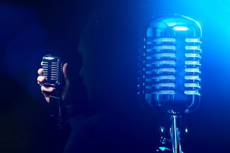 Metal microphone on a blue background. The singer sings a song on a dark stage.