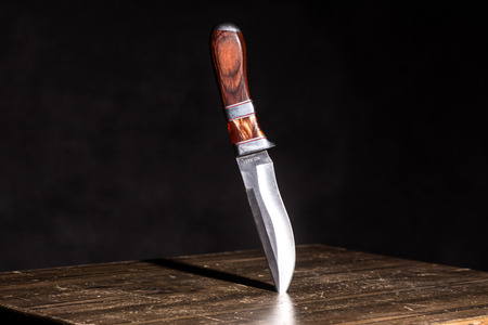 war decoration: Knife stuck in a table on a black background. Stock Photo