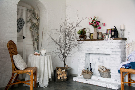 design interior: The design interior rustic room with a fireplace, flowers, chairs and a table with cups of tea. Stock Photo