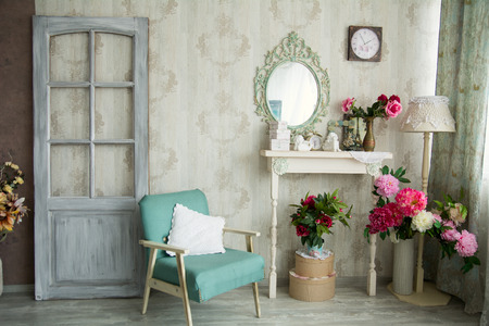 country house style: Vintage country house interior with mirror and a table with a vase and flovers. Interior design with a door and an old chair. Stock Photo