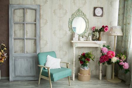 Vintage landhuis inter met spiegel en een tafel met een vaas en flovers. Inter ontwerp met een deur en een oude stoel.