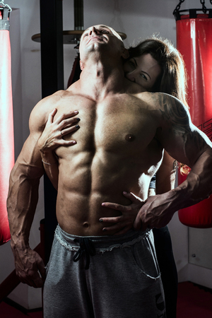 necking: Woman passionately embraces muscular man in the gym. Handsome bodybuilder with a woman Stock Photo