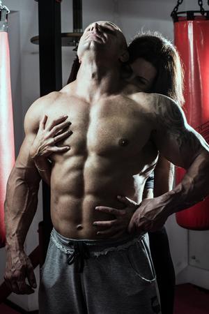 pareja apasionada: La mujer abraza apasionadamente hombre muscular en el gimnasio. Foto de archivo