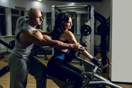 chest women: Sport, fitness, bodybuilding, teamwork and people concept - woman and personal trainer flexing muscles on gym machine.