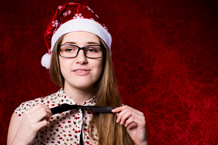 santa hat: Upset girl with glasses in a santa hat on a red background.