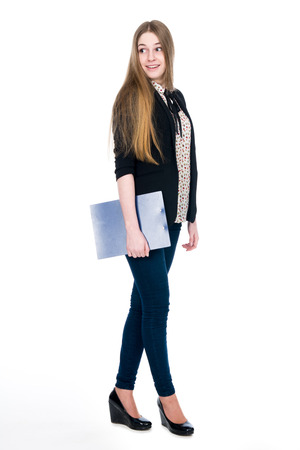 holding back: Full length of young blond smiling girl holding clipboard surprise looking back. Isolated on white background Stock Photo
