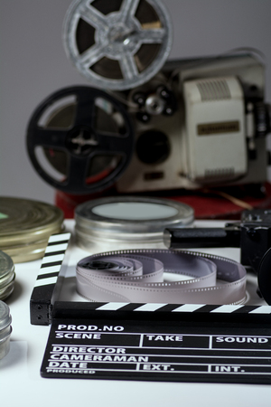 cine: Old retro camera, film clapper, rolls of film and a 35mm boxes for films and film projector. Set for shooting and film screenings Stock Photo