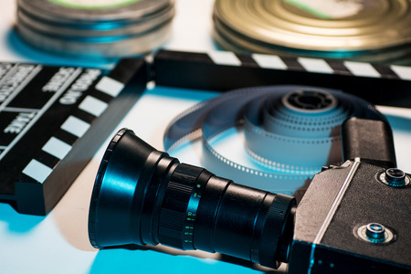 35mm: Old retro camera, film clapper, rolls of film and a 35mm box films. Stock Photo