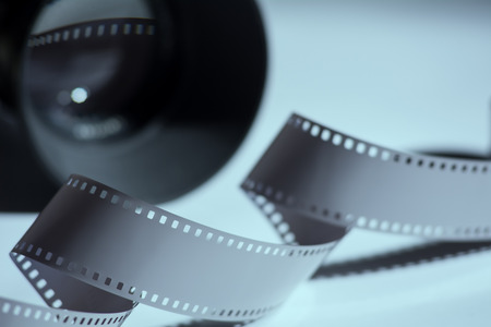 spun: Close-up reel of film and spun in the background camera lens. Stock Photo