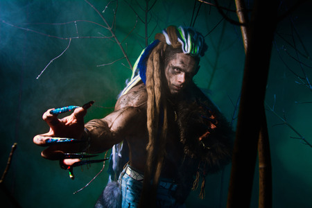 long nails: Muscular werewolf with dreadlocks with long nails among the branches of the tree and smoke. Gothic image of scary diabolical creatures for Halloween