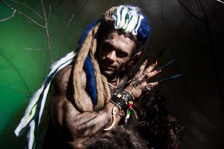 unas largas: Hombre lobo con las u�as largas entre las ramas del �rbol y el humo. imagen g�tica de criaturas diab�licas de miedo para Halloween